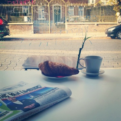 Ontbijten in bur o bar met croissant en krant